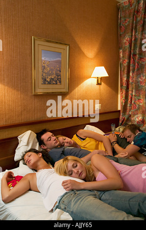Friends asleep on hotel bed - Stock Photo