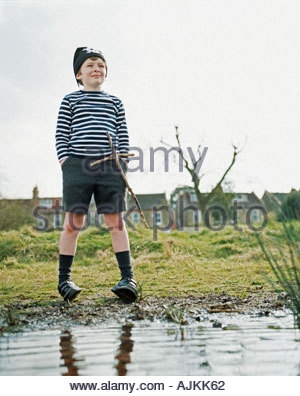 Boy standing at the edge of a pond - Stock Photo