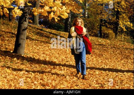 Beautiful blond walking through field of fallen autumn leaves in Sweden - Stock Photo
