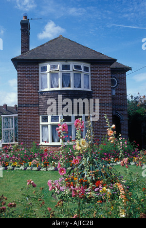 Evercreech Somerset England 1920s 30s detached house of brick with summer front garden flowers lawn west country - Stock Photo