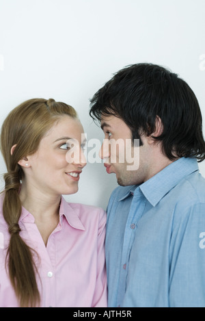 Young couple making goofy faces at each other, head and shoulders, portrait - Stockfoto
