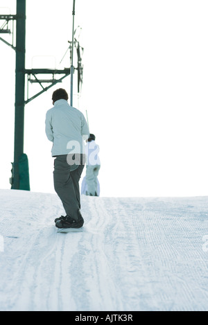 Snowboarder going up hill on ski lift, rear view - Stock Photo