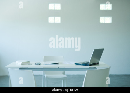 Laptop computer and cell phone on desk in office - Stock Photo