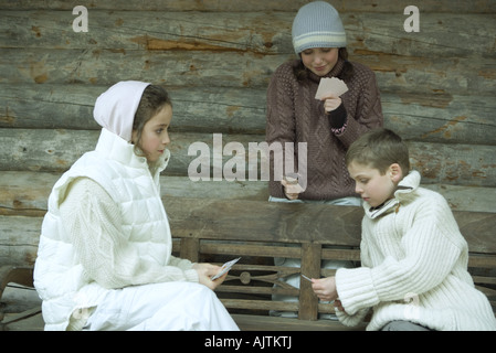 Young friends in winter clothes playing cards - Stockfoto