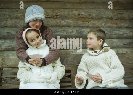 Young friends in winter clothes playing cards - Stock Photo
