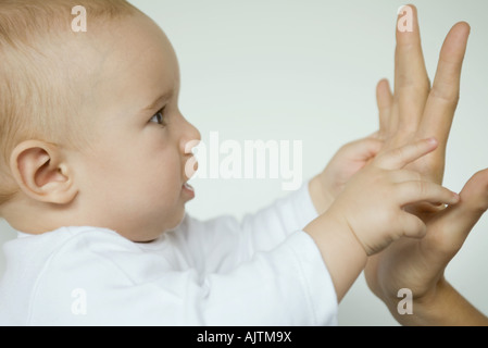 Baby reaching for mother's hand, profile view, close-up - Stockfoto
