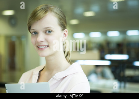 Young female college student in library, smiling at camera, head and shoulders - Stock Photo