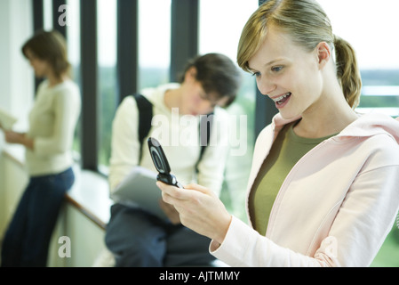 Female college student looking at cell phone, smiling - Stockfoto