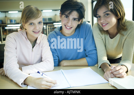 Three college students studying together in library, smiling at camera, portrait - Stock Photo