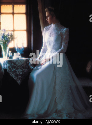 Young woman in long white bridal gown seated by window. - Stock Photo