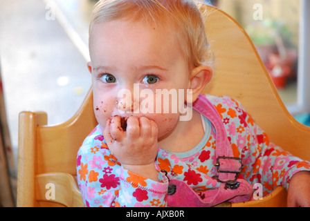 Baby eating chocolate cake messily - Stock Photo