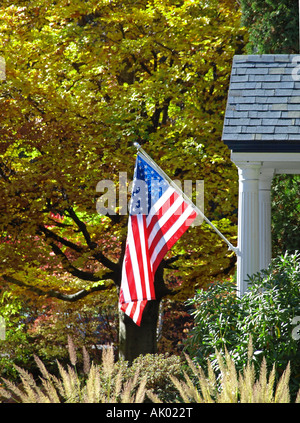 An American Flag Hangs From A Front Porch In A Neighborhood Of Stock