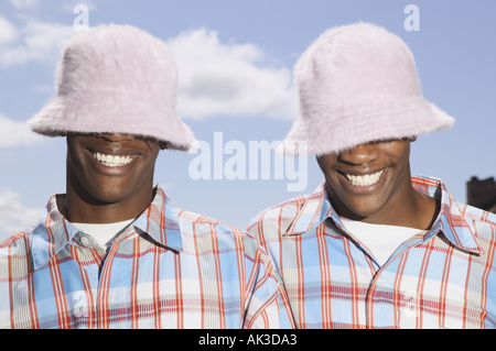 Twin teenage boys in matching hats and shirts - Stock Photo