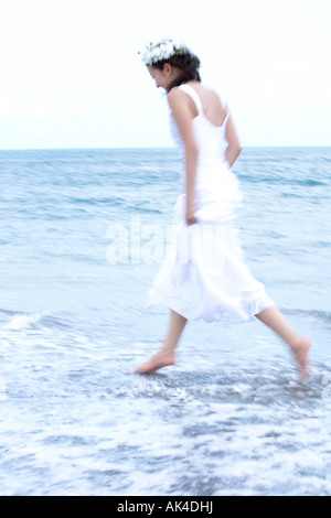 Bride running by the beach - Stock Photo