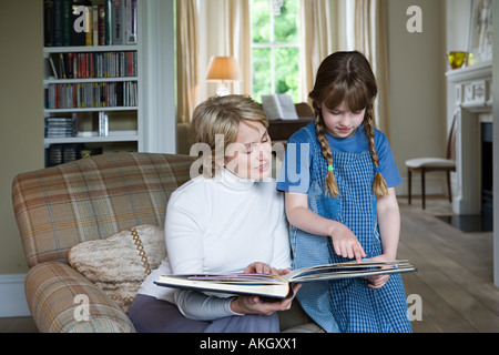 Girl and grandmother looking at scrapbook - Stock Photo