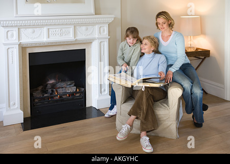 Female relatives looking at photograph album - Stock Photo