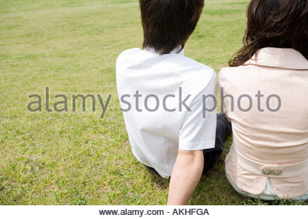 Couple sitting on grass - Stock Photo