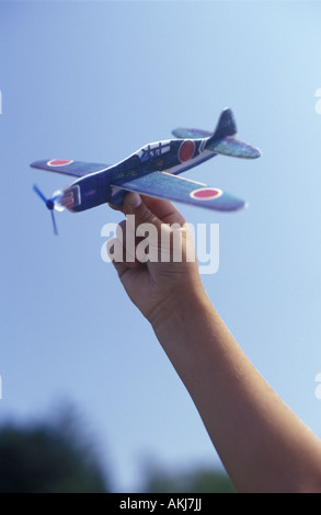 Boy playing with a toy airplane - Stockfoto
