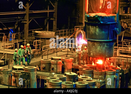 Workers pour molten steel into molds at a scrap metal foundry in Pittsburg - Stock Photo