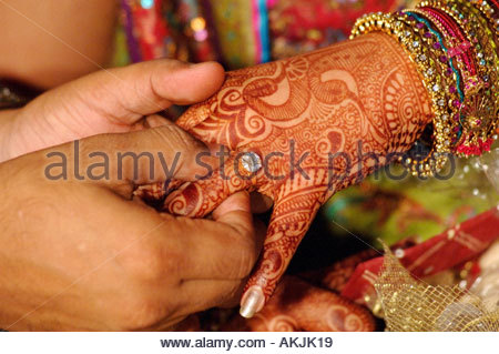 Bridegroom putting wedding ring on finger of bride hand decorated with heena India - Stock Photo