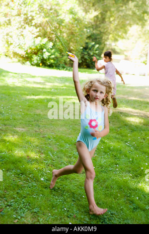 Girl in bathing suit flying kite - Stock Photo