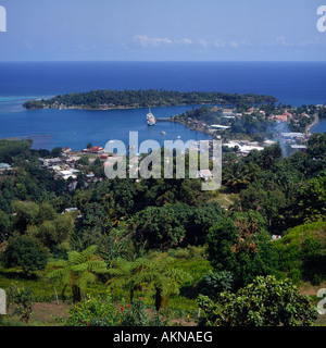 View from hill over trees town sea and natural harbour with clear blue skies at Port Antonio north east Jamaica - Stock Photo