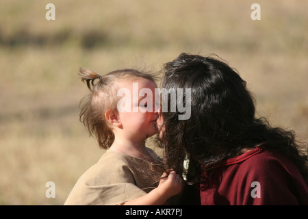 A Native American Indian mother kissing her daughter - Stock Photo