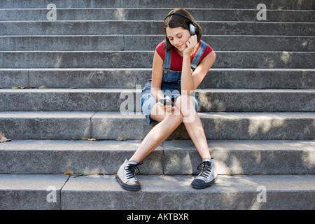 Teenage girl listening to an mp3 player - Stock Photo