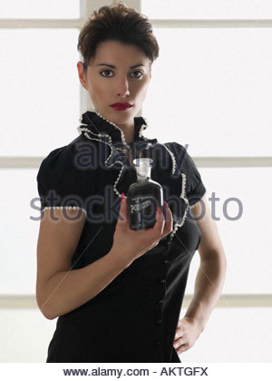 Woman holding a bottle of poison - Stock Photo