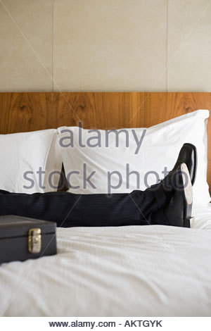 Legs of businessman on bed - Stock Photo