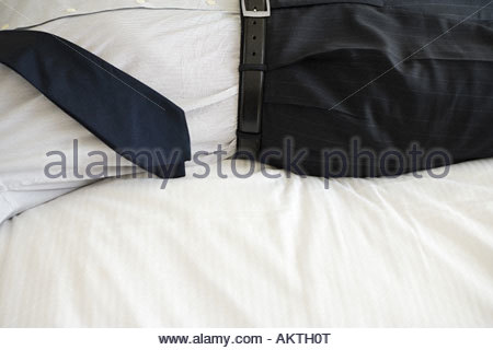 Businessman lying on bed - Stock Photo