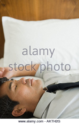 Businessman sleeping on bed - Stock Photo