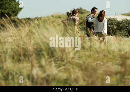 Group of friends walking through dunes, rear view - Stock Photo