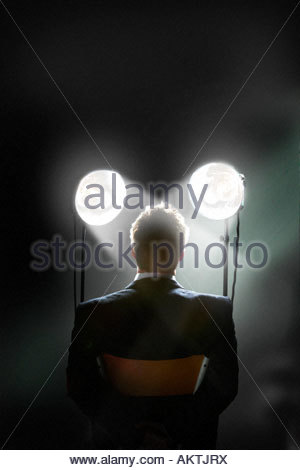 Interrogation scene with spotlights shining in a man's face - back view of restrained businessman - Stock Photo