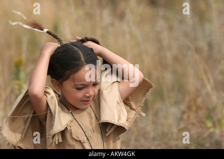 A male portrait of a young Native American Sioux Indian boy fixing his braids outside in South Dakota during the - Stock Photo