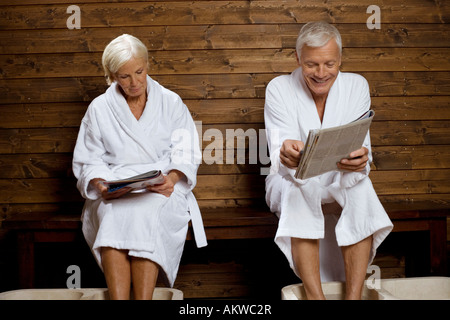 Germany, senior couple reading magazine in spa - Stock Photo