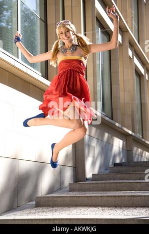 Woman jumping of joy, wearing red dress - Stock Photo