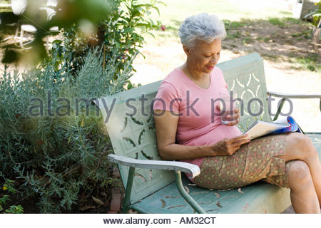Woman on patio with magazine and glass of water - Stock Photo
