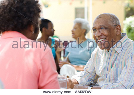 Two generations of couples sitting outdoors talking - Stock Photo
