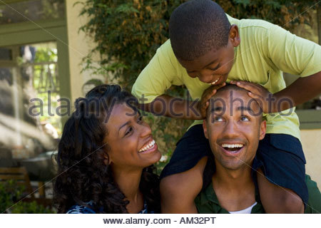 Man piggybacking young boy and standing beside woman - Stock Photo