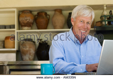 Man at laptop with mug smiling - Stock Photo