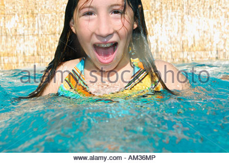 Girl in swimming pool with mouth open - Stock Photo