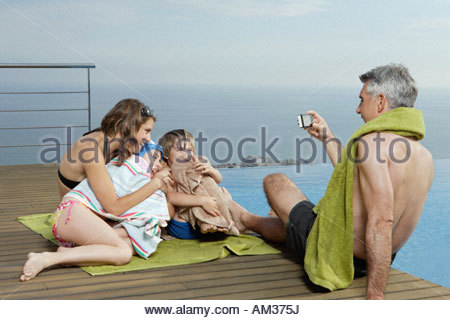 Man with woman and two kids on deck taking picture - Stock Photo