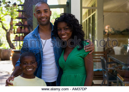 Couple with young boy outdoors smiling - Stock Photo