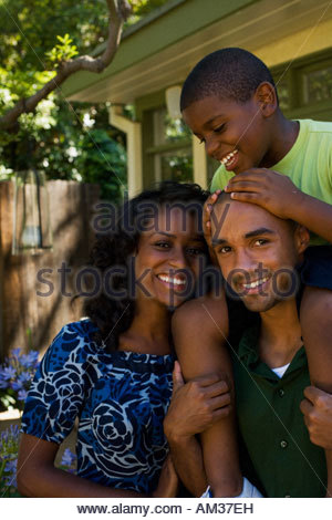 Man piggybacking young boy with mother beside him - Stock Photo