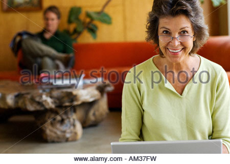 Woman at laptop with man in background reading - Stock Photo