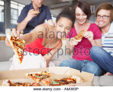 Four friends eating pizza in living room - Stock Photo