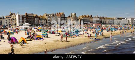 At a British seaside beach in summer, Weymouth beach, Dorset, England, UK - Panorama - people sunbathing and swimming - Stock Photo