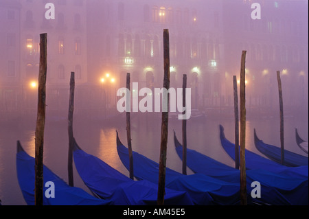 Italy Venice The Grand Canal with gondolas moored at dusk in the fog - Stock Photo