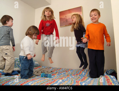 boys and girls playing in their room jumping on the bed - Stock Photo
